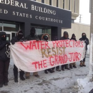 "People stand outside the federal building in North Dakota. They are holding a banner that says ""Water Protectors Resist the Grand Jury."""