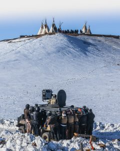 Photo shows armed state security forces behind an armored personnel carrier, in the far distance is a cluster of traditional tents and silhouettes of water protectors. Between the two groups is a field of snow.